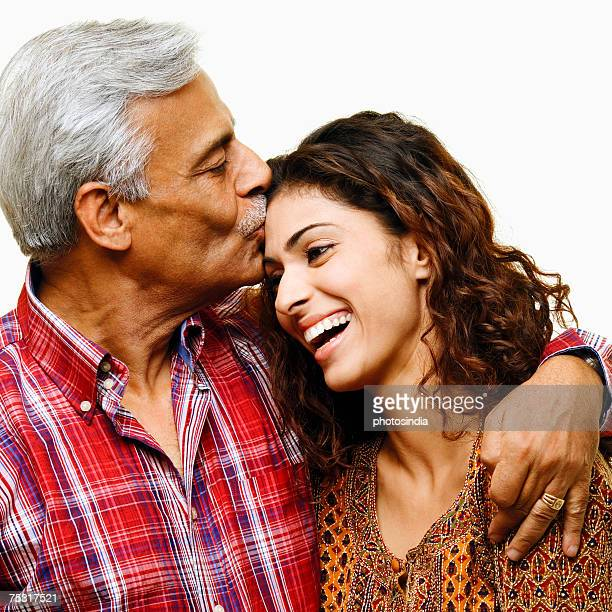 Close-up of a senior man kissing his daughter on the forehead