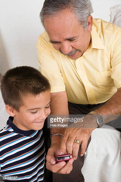 Close-up of a senior man showing a mobile phone to his grandson