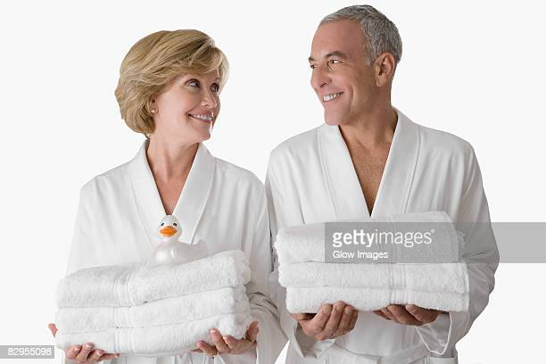 Close-up of a senior man with a mature woman standing together and holding folded towels