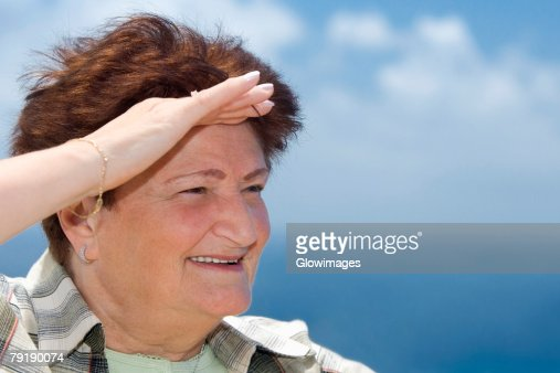 Close-up of a senior woman saluting : Stock Photo
