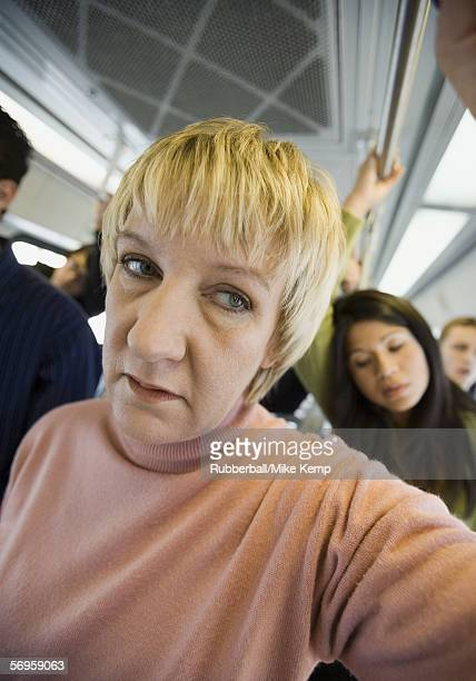 Close-up of a senior woman standing in a commuter train