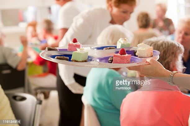 Close-up of a senior woman's hand holding a plate of dessert dishes at a lady's luncheon