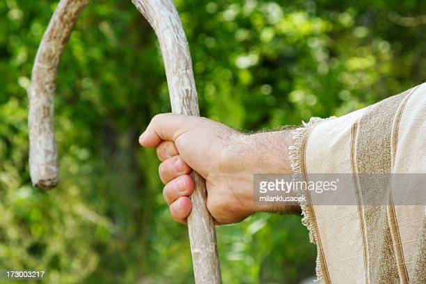 Closeup of a shepherd's hand holding a wooden crook