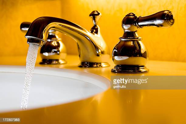 A close-up of a silver faucet sink in a yellow bathroom