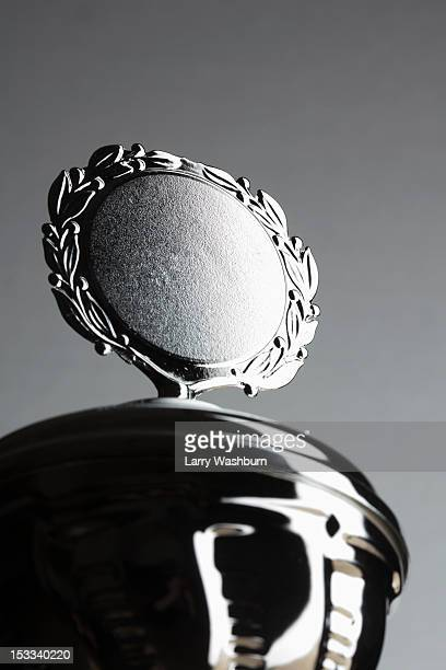 Close-up of a silver trophy with blank plaque surrounded by laurel wreath