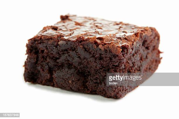 Close-up of a single chocolate brownie on a white surface