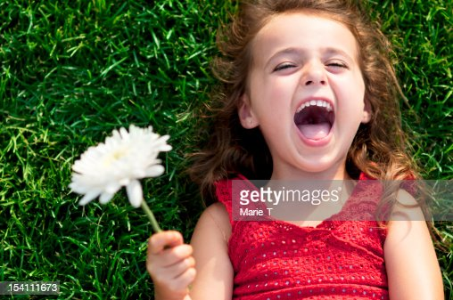 Close-up of a smiling little girl laying on the grass : Stock Photo