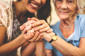 Close-up of a smiling nurse holding a senior woman's hand