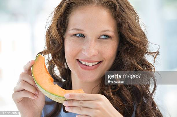 Close-up of a smiling woman eating melon
