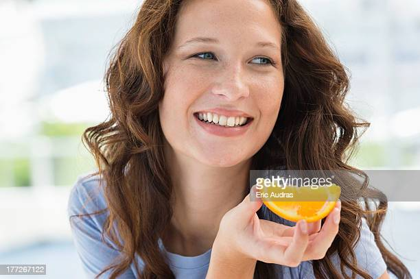Close-up of a smiling woman holding a slice of an orange