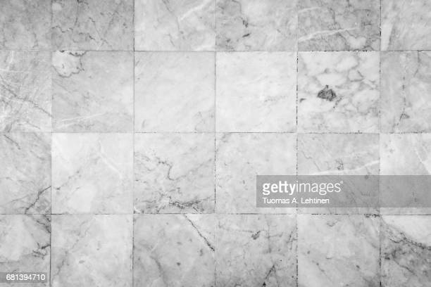 Close-up of a smooth marble floor with vignetting viewed from above in black&white.