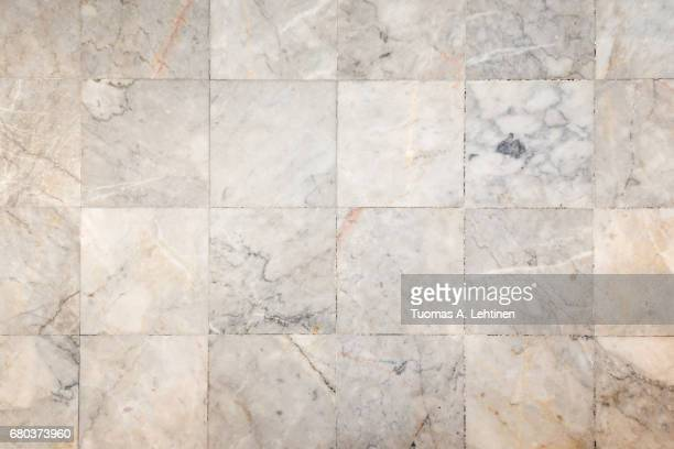 Close-up of a smooth marble floor with vignetting, viewed from above.