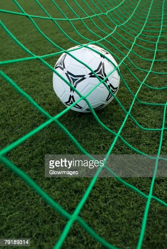 Close-up of a soccer ball in a goal post net : Foto de stock