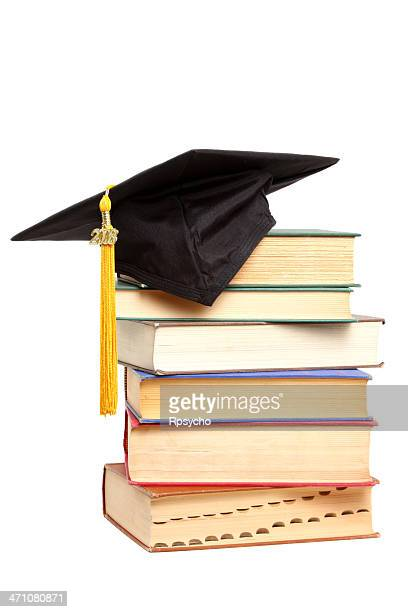 Close-up of a stack of books with a graduation cap atop it
