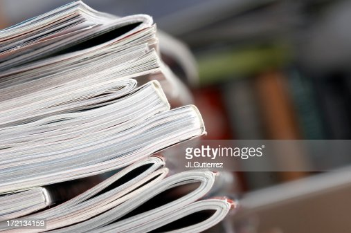 A closeup of a stack of magazines on a table