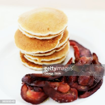 close-up of a stack of pancakes served with bacon : Stock Photo