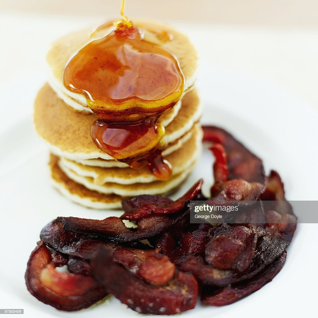 Close-up of a stack of pancakes served with syrup and bacon : Stock Photo