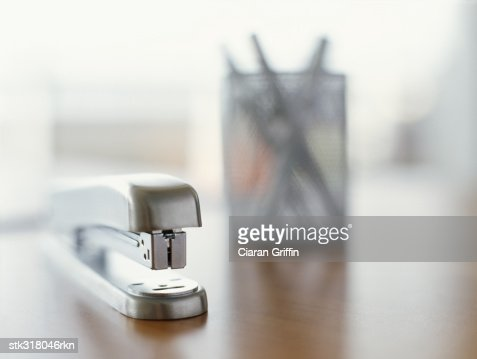 close-up of a stapler and pen stand on a table in an office