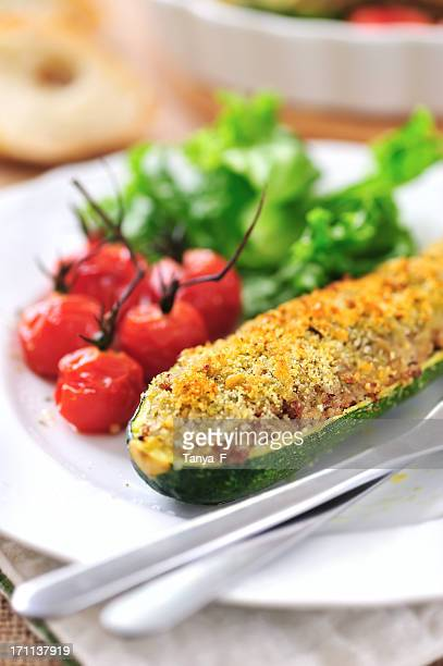 Closeup of a stuffed zucchini served with tomatoes and salad