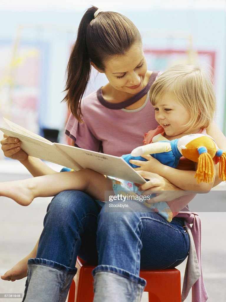 Close-up of a teacher reading to a child : Stock Photo