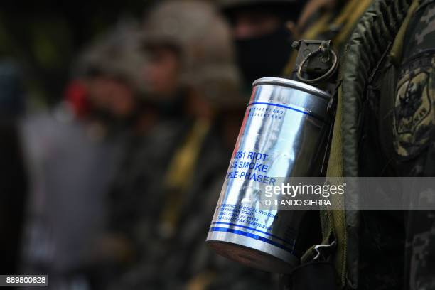 Closeup of a tear gas canister belonging to an Honduran riot police officer who stands alert as supporters of presidential candidate for Honduras'...