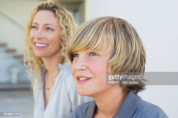 Close-up of a teenage boy smiling with his mother