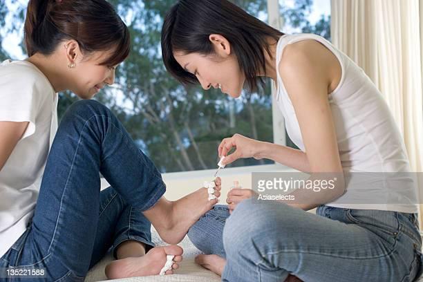 Close-up of a teenage girl applying nail polish to another teenage girl's toenails