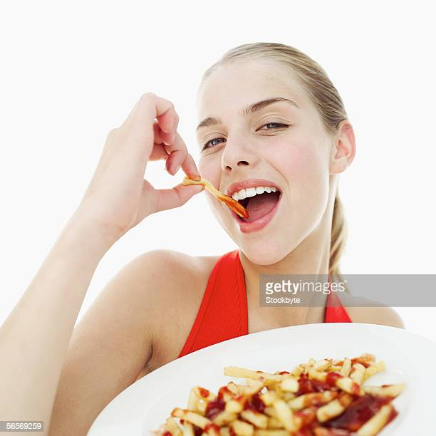 close-up of a teenage girl eating french fries with ketchup