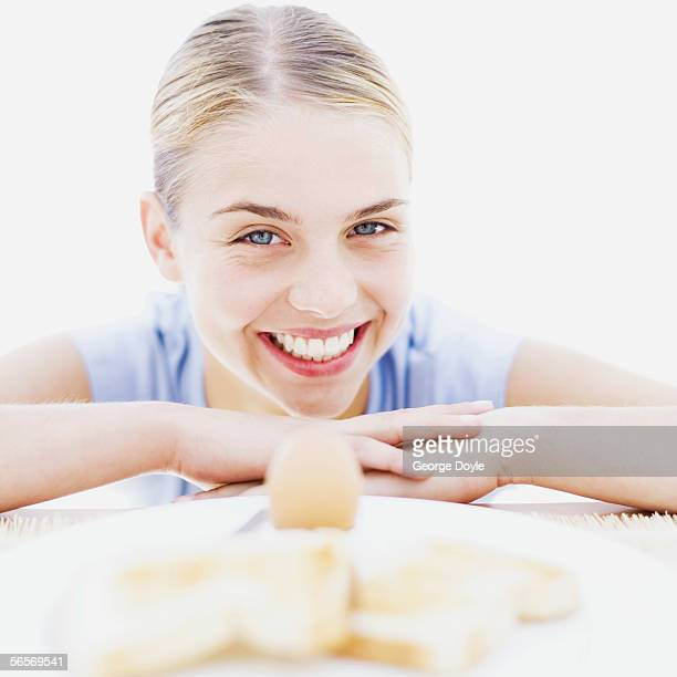 close-up of a teenage girl in front of a plate of boiled egg and toast