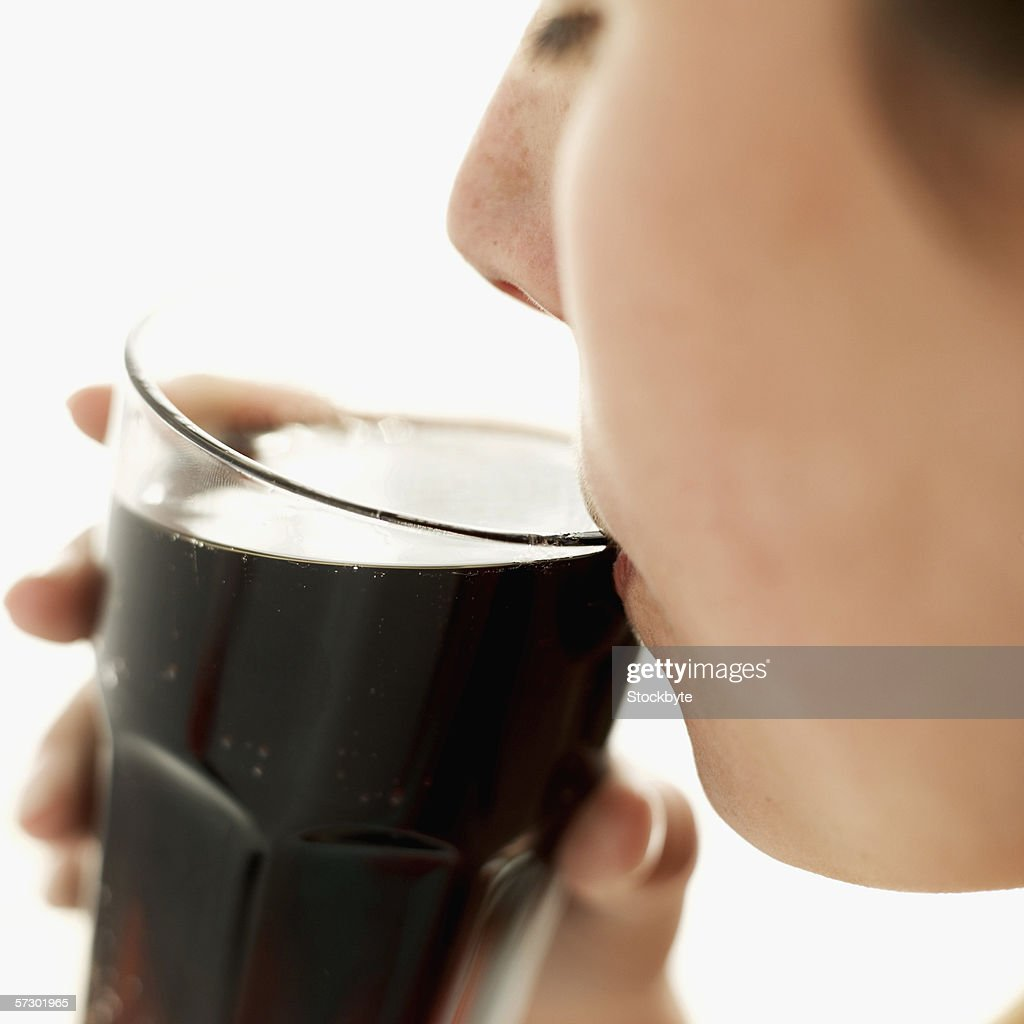Close-up of a teenage girl (15-17) sipping a glass of cola : Stock Photo