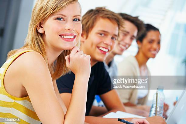 Close-up of a teenage girl smiling with friends in classroom
