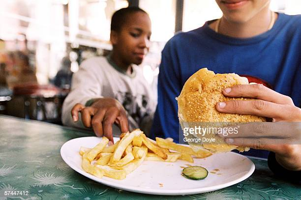 close-up of a teenagers hand stealing a French fry from someone else's plate