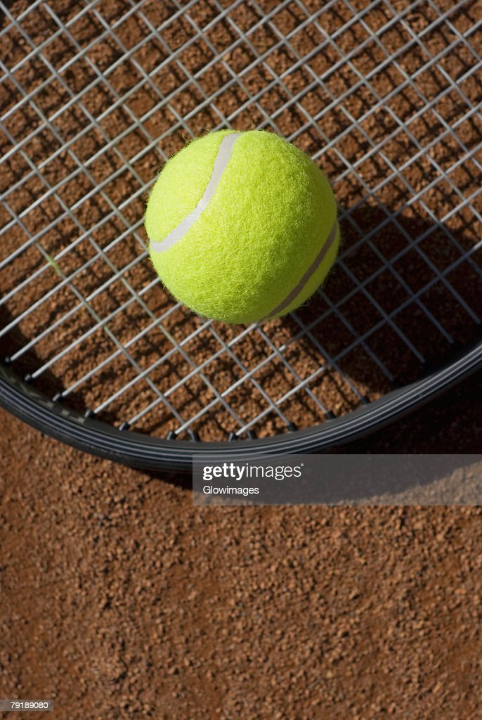 Close-up of a tennis ball on a racket in a court : Stock Photo