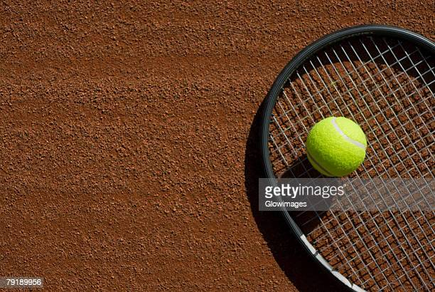 Close-up of a tennis ball on a racket in a court