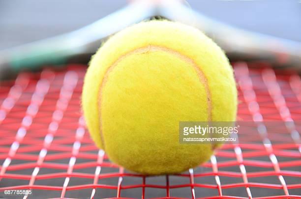 Close-up of a tennis ball on a tennis racquet