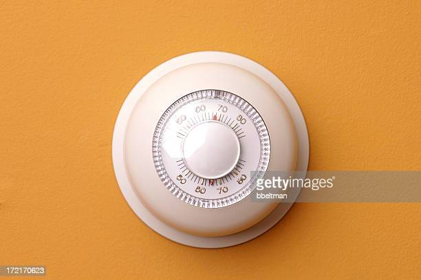 A closeup of a thermostat on a orange wall set to 68 degrees