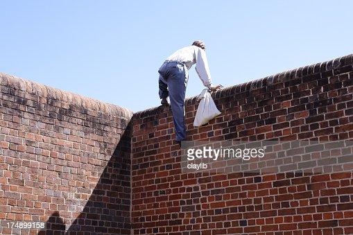 Close-up of a thief climbing over a brick wall