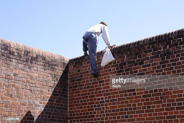 Close-up of a thief climbing over a brick wall
