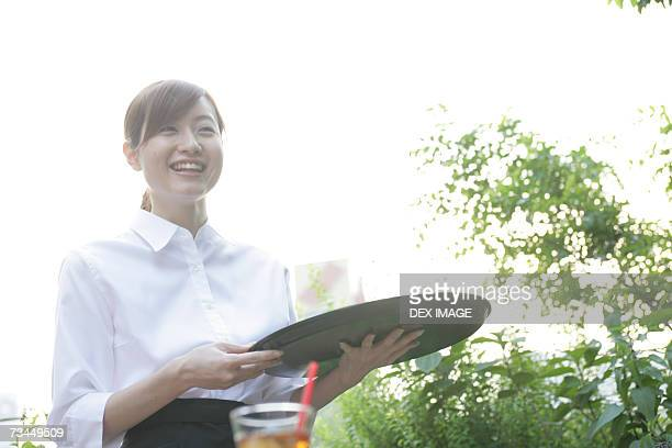 Close-up of a waitress holding a serving tray and smiling