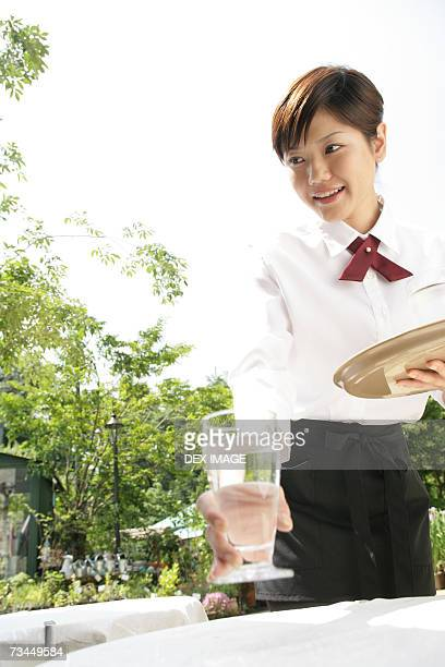 Close-up of a waitress serving water on the table