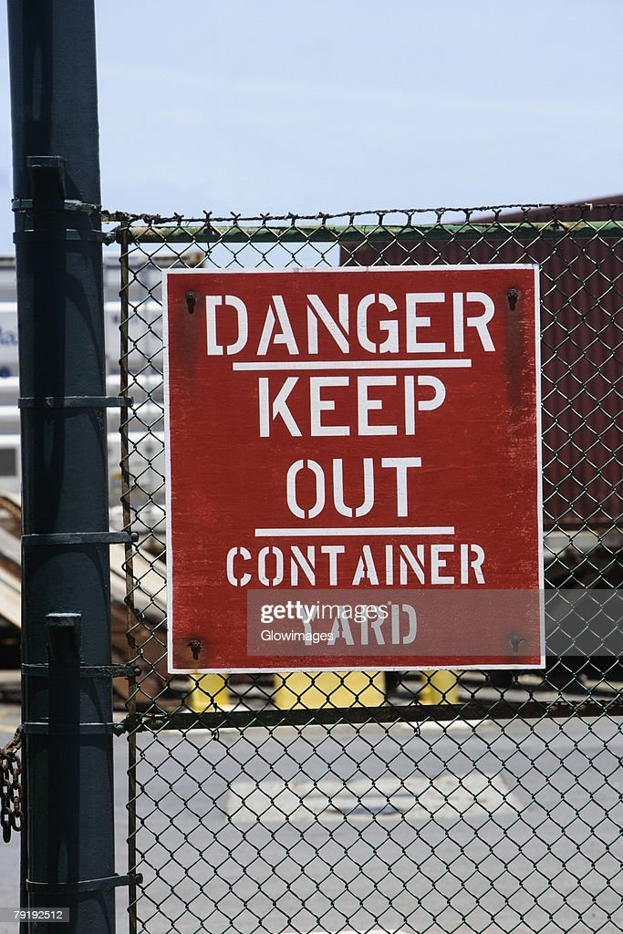 Close-up of a warning sign on a chain-link fence