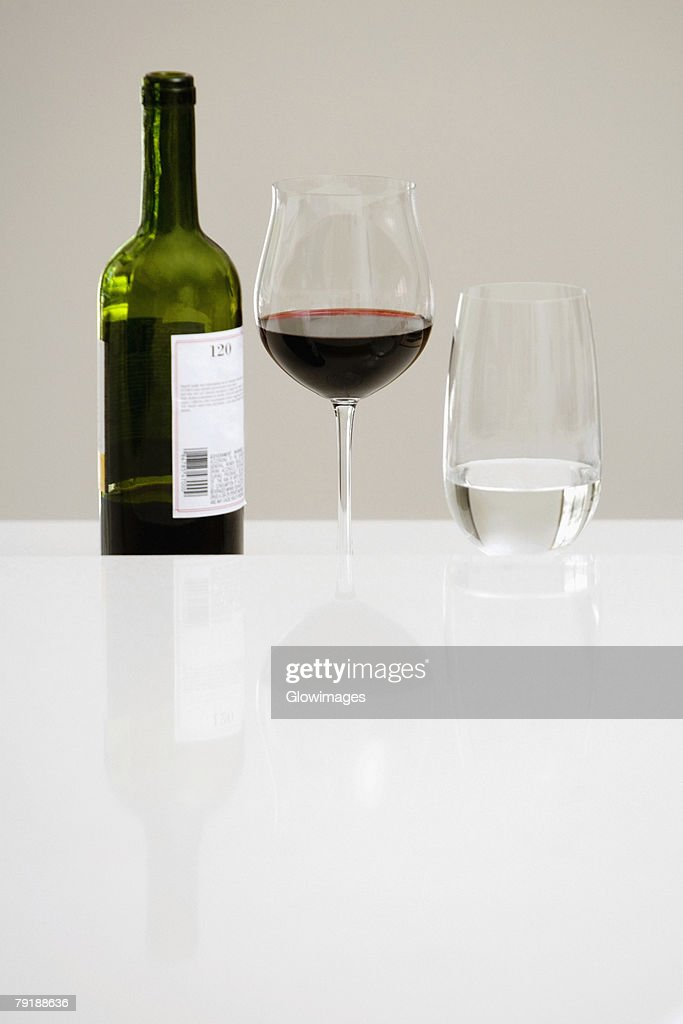Close-up of a wine bottle with a glass of red wine and a glass of water on a dining table : Stock Photo