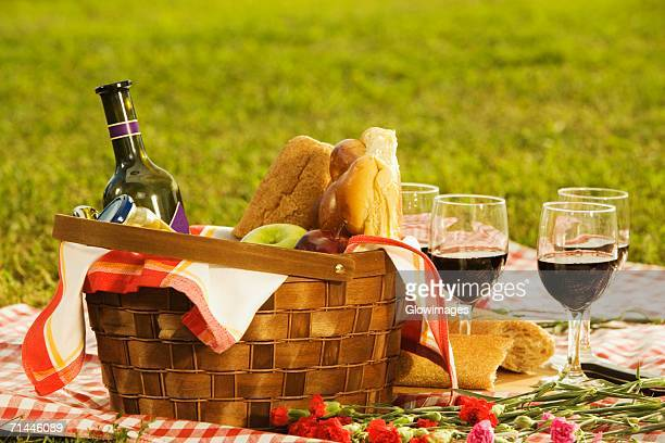 Close-up of a wine bottle with bread and fruits in a picnic basket