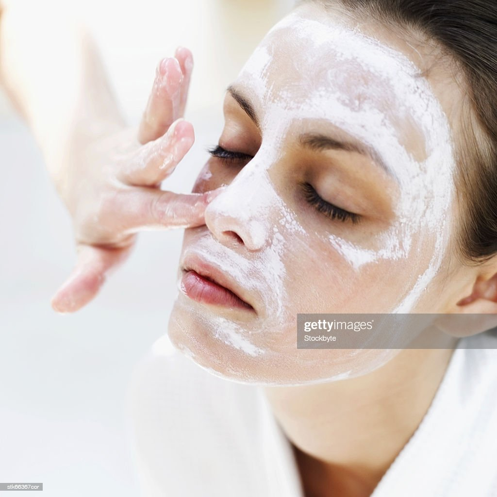 close-up of a woman applying face pack : Stock Photo