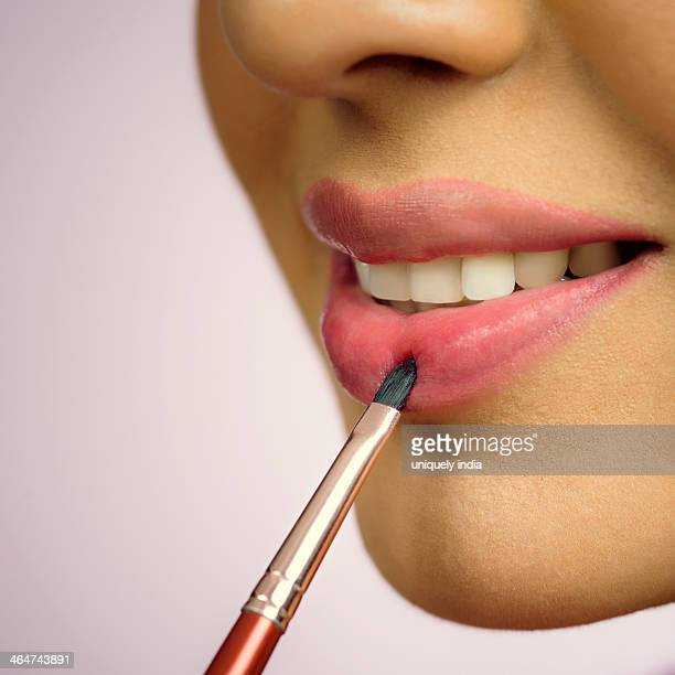 Close-up of a woman applying lip liner on her lips