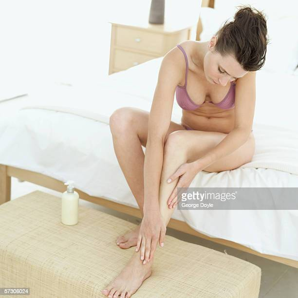 Close-up of a woman applying lotion on her leg sitting on a bed in underwear