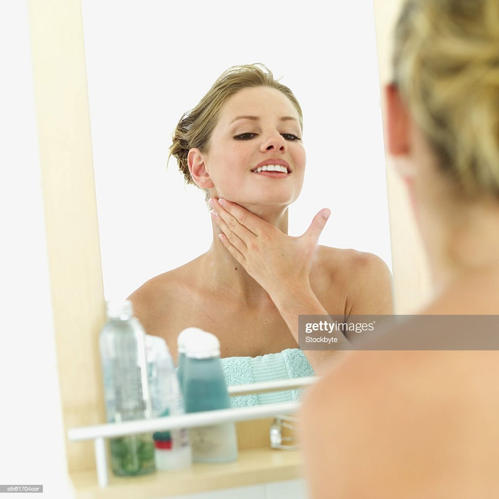 close-up of a woman applying moisturizer on her neck : Stock Photo