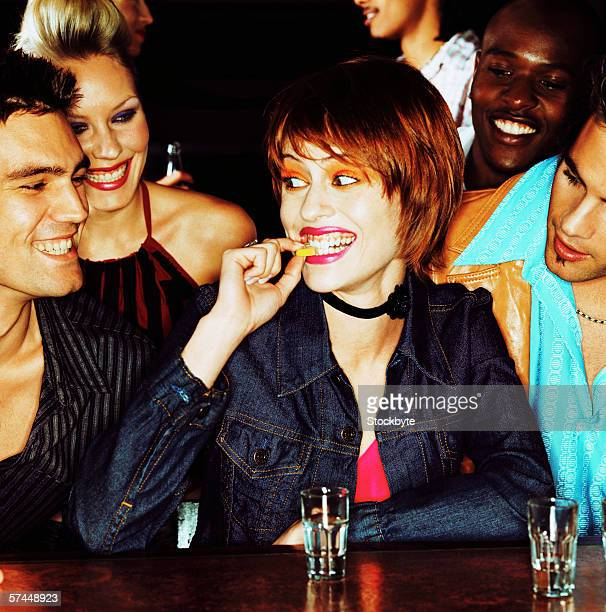 close-up of a woman biting a lemon rind before a shot at a bar with friends