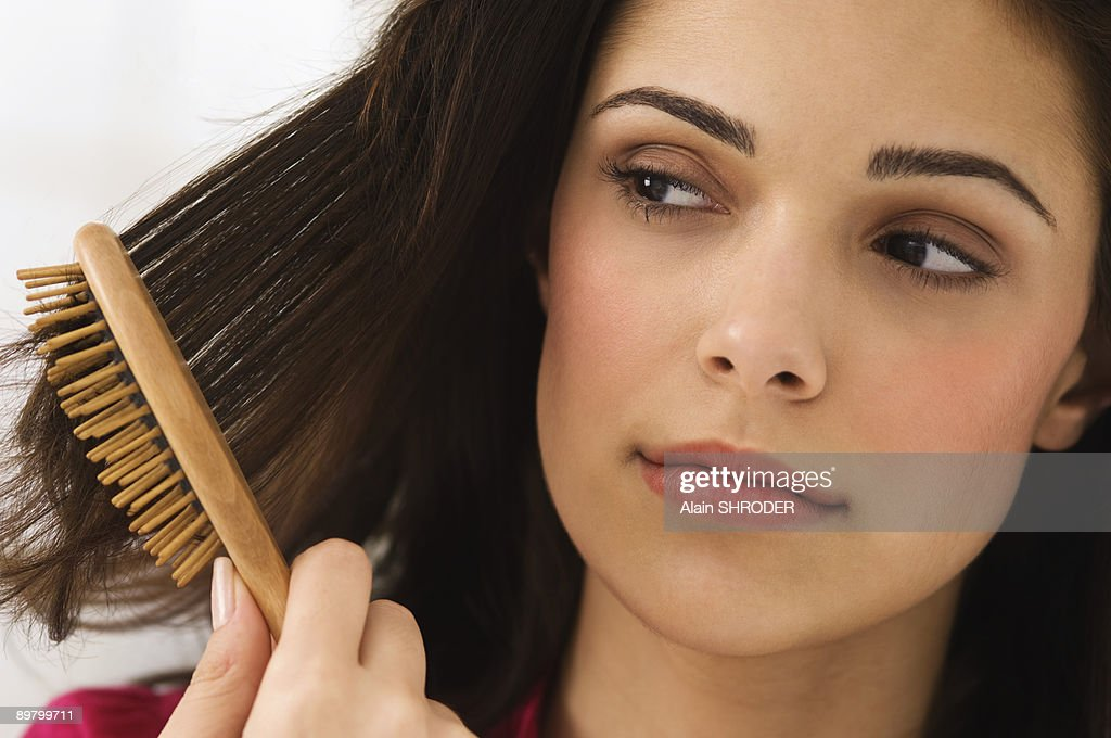 Close-up of a woman brushing her hair : Stock Photo