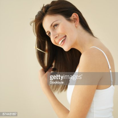 Close-up of a woman combing her hair : Stock Photo
